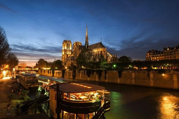 Foto di una barca sulla Senna e Cattedrale di Nôtre Dame sullo sfondo