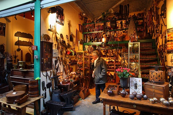 Immagine di un uomo in un mercato pieno di antichità e oggetti per la casa