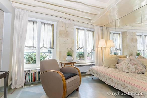 Immagine del salotto bianco dell'appartamento PA-3974, con finestre francesi e travi in vista in legno bianco.