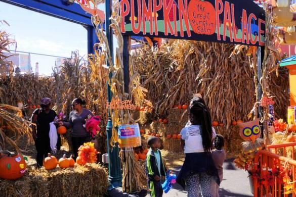 Immagine di bambini in un area piena di fieno e di zucche nel Luna Park a Coney Island