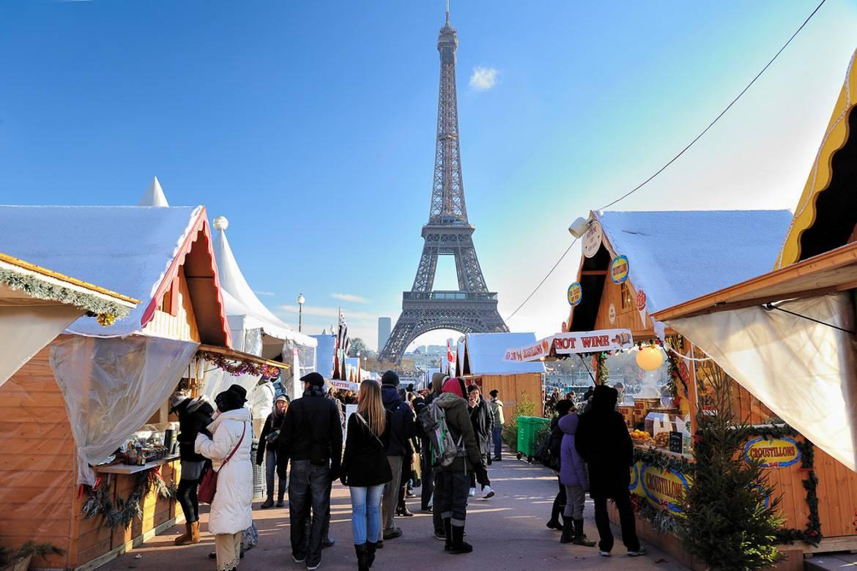 Immagine delle bancarelle a forma di cottage alpini ai mercatini di Natale con la Torre Eiffel sullo sfondo