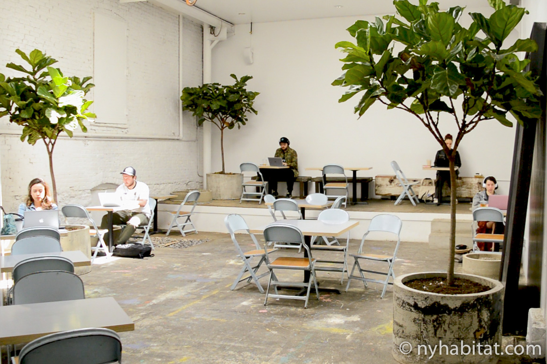 Immagine di persone sedute ai tavolini con computer portatili e caffè.