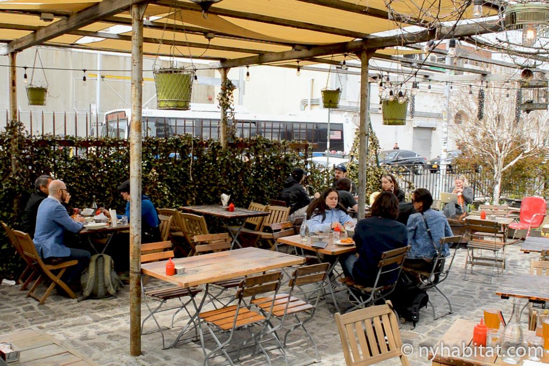 Immagine di persone che mangiano all'aperto su tavolini di legno sotto una pergola al Forrest Point