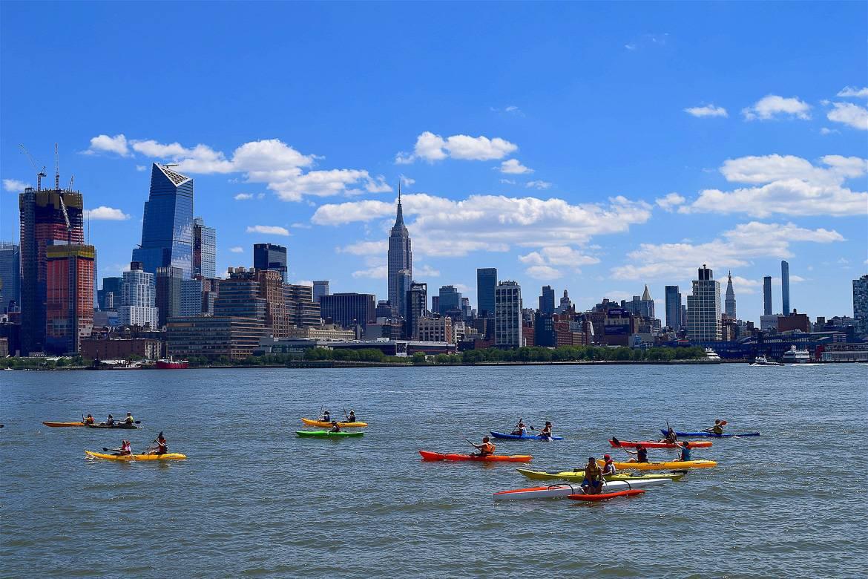 Immagine di persone sui kayak sul fiume a New York con lo skyline della città sullo sfondo.
