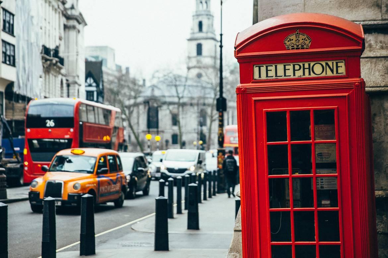 Immagine di una cabina telefonica rossa di Londra con un taxi sullo sfondo.