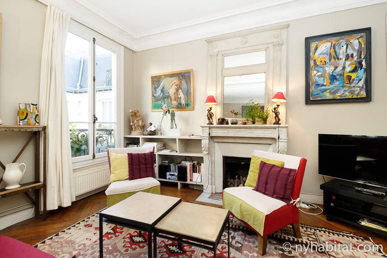 Immagine del soggiorno di PA-3554 con due poltrone, camino ornamentale e opere d'arte.