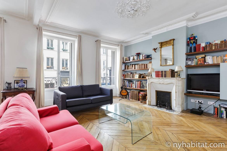 Immagine del soggiorno in PA-4690 con divano, camino, librerie e finestre alla francese.