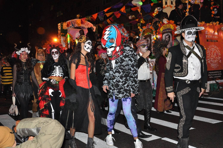 Immagine di persone con i volti dipinti e costumi di Halloween che partecipano alla Village Halloween Parade.