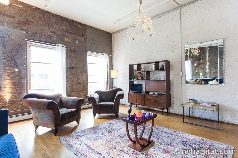 Immagine di un salotto a NY-16930 con poltrone, specchio, libreria e lampadario.