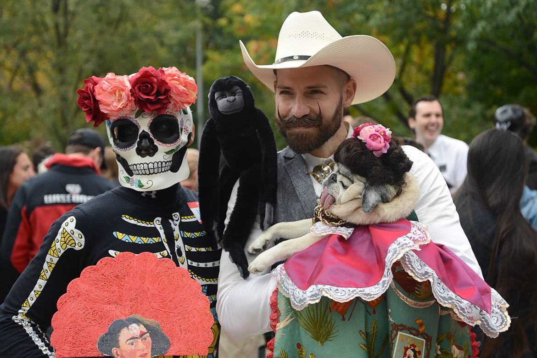 Immagine di una coppia e un cane con costume da Halloween nell'East Village