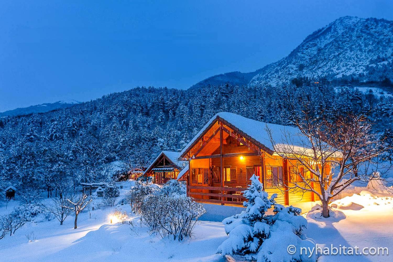 Immagine notturna dell'esterno dello chalet in affitto PR-954 ricoperto di neve.