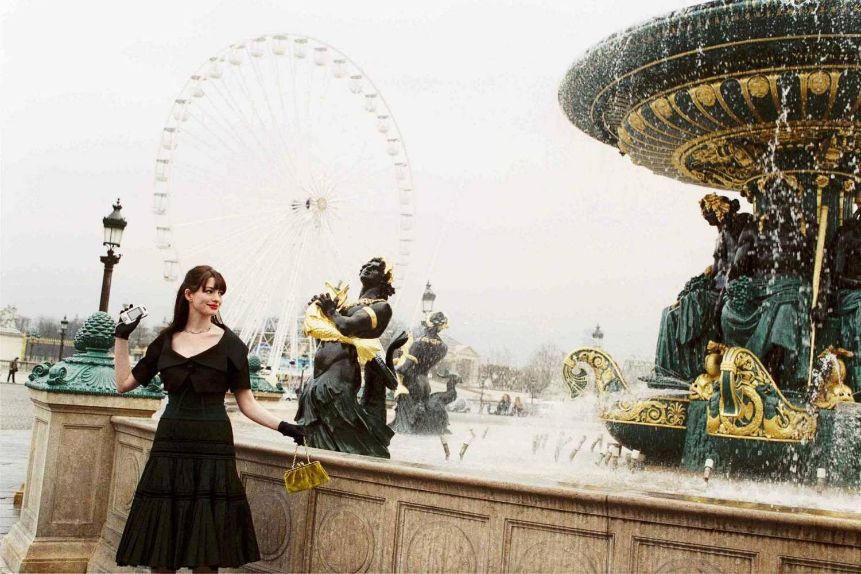 Fermo immagine dell'attrice Anne Hathaway in una scena de il Diavolo Veste Prada presso la fontana di Place de la Concorde.