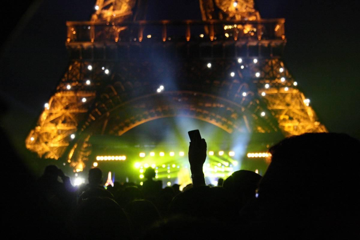 Immagine notturna della folla davanti alla Torre Eiffel illuminata.