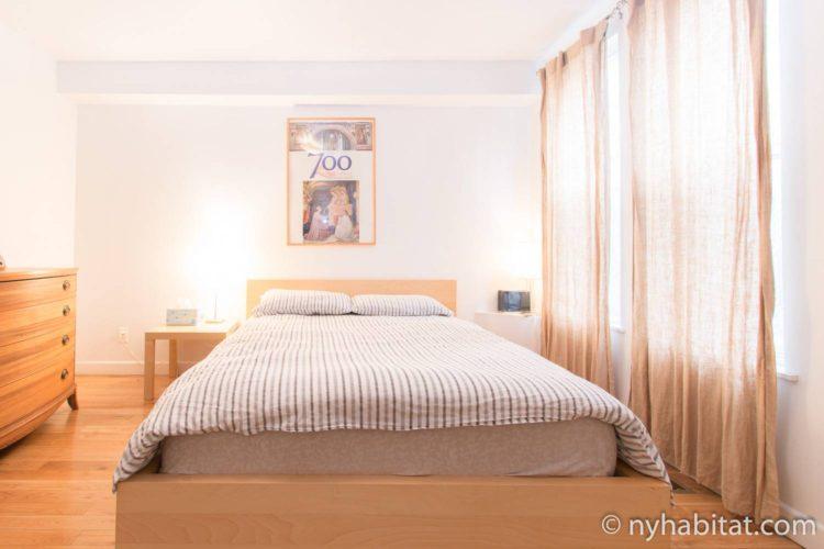 """Immagine della camera da letto della NY-14720 con letto """"queen"""" e finestre con tende."""