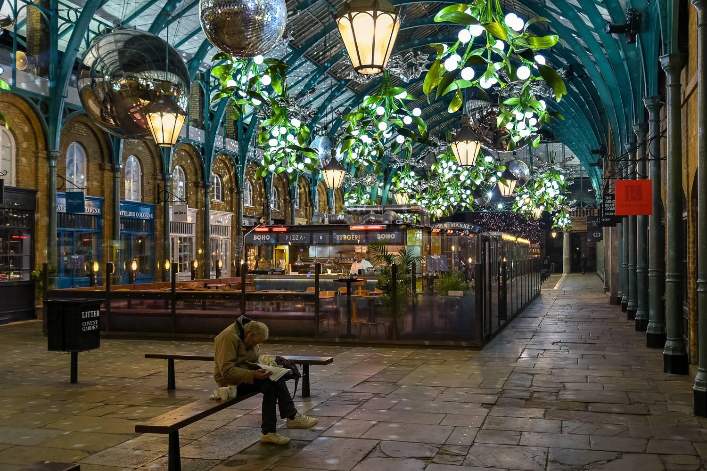 Immagine del mercato di Covent Garden decorato per le festività con mazzi di vischio illuminati.