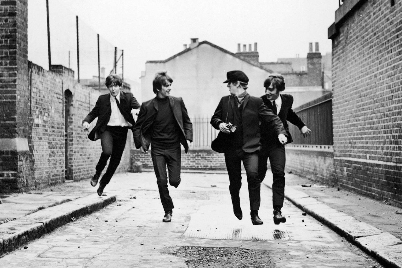 Immagine dei Beatles mentre corrono attraverso un vicolo di Notting Hill nel film Tutti per uno.
