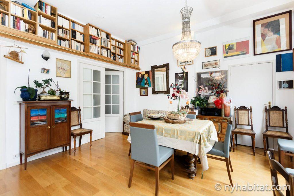 Immagine di uno spazio abitativo in PA-1460 con tavolo e sedie, lampadario e mensola per libri.