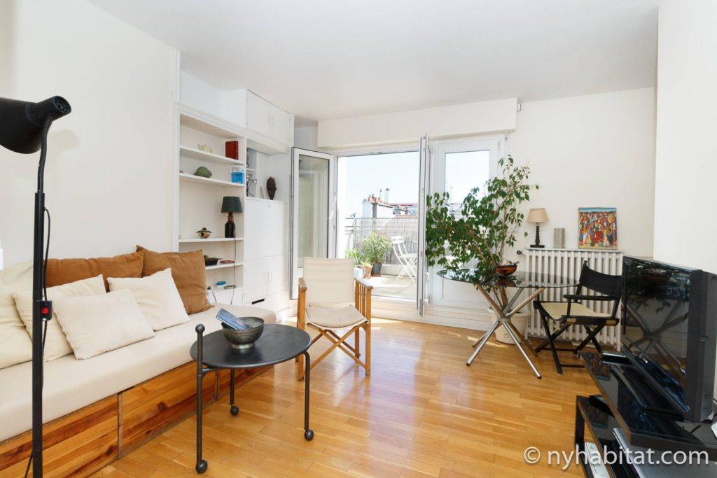 Immagine di uno spazio abitativo in PA-3384 con divano, sedie, tavoli e mensole per i libri.