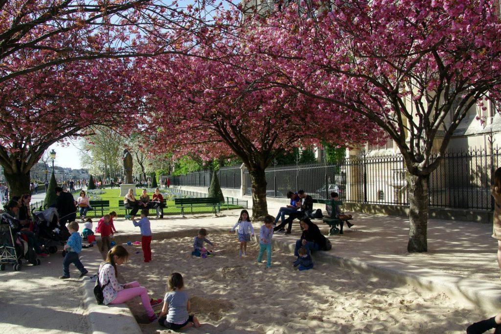 Immagine di bambini che giocano un parco di Parigi in primavera.