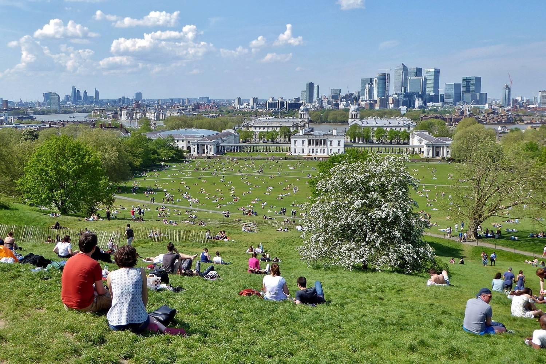 Immagine di gente che siede sulla collina a Greenwich Park davanti all'orizzonte di Londra in un giorno assolato di primavera.