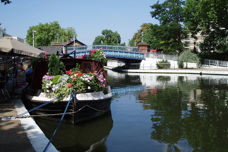 Immagine di una barca con fiori ormeggiata al Regent's Canal a Londra.