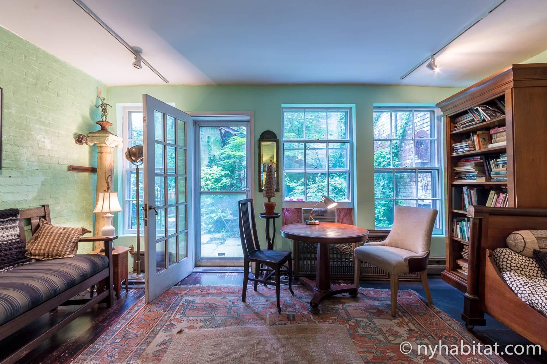 Immagine del salone di NY-15343 con un tavolo con sedie, ripiani per libri e divani.