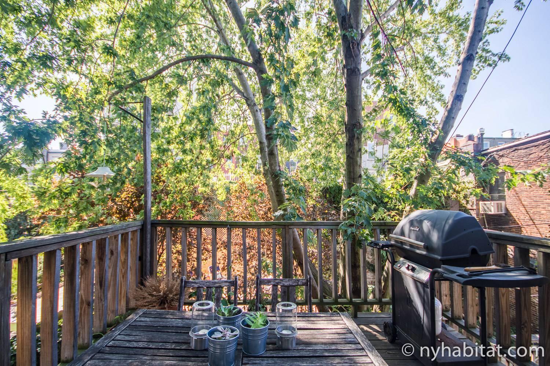 Immagine del patio den giardino sul retro di NY-15411 con griglia e un tavolo con sedie.