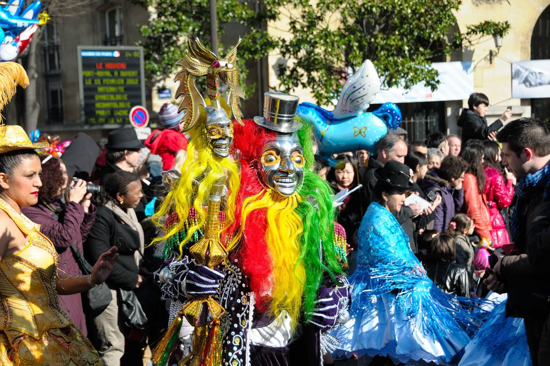 Immagine di persone con maschere e parrucche colorate che marciano nella parata del Carnaval de Paris.