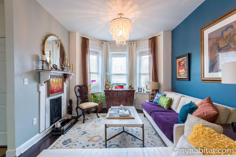 Immagine del soggiorno del NY-17903 con divano e caminetto decorativo.