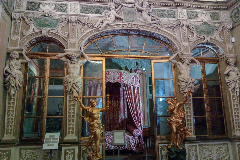 Immagine della facciata di una stanza nel Palazzo Lascaris decorato con sculture di Cherubini e dettagli d'oro.