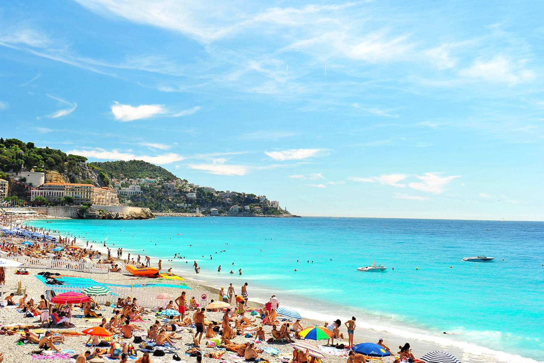 Immagine di una spiaggia di Nizza con persone sulla sabbia e barche in acqua.
