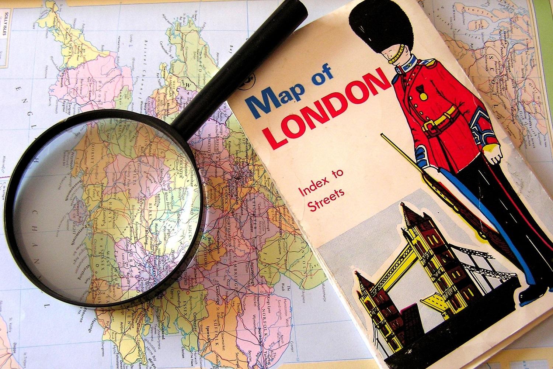 Immagine di una lente di ingrandimento e di una guida londinese su una mappa della Gran Bretagna.