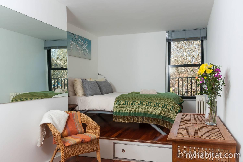 Immagine della camera da letto dell'appartamento, che con i suoi tocchi verdi e arancioni sembra essere fatta apposta per l'autunno.