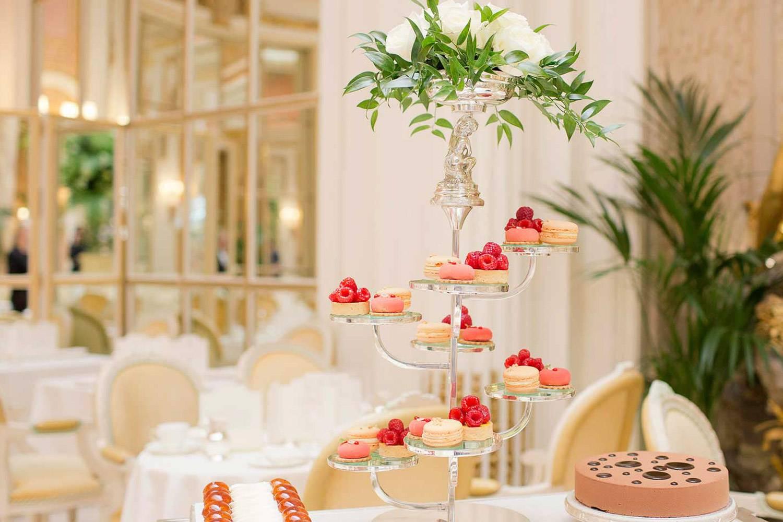 Immagine di delicati pasticcini con sullo sfondo l'elegante sala da pranzo del Ritz di Londra.