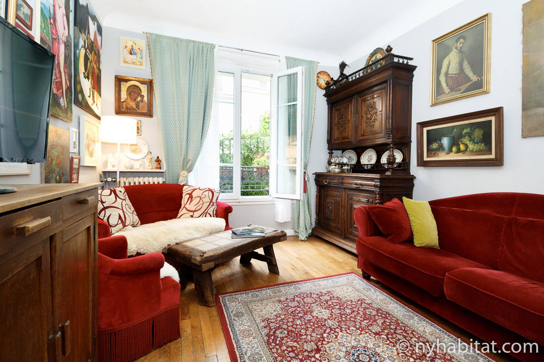 Immagine del salotto di Montmartre, casa vacanze di Parigi PA-3387 con il suo mobilio rosso e accenti vintage.