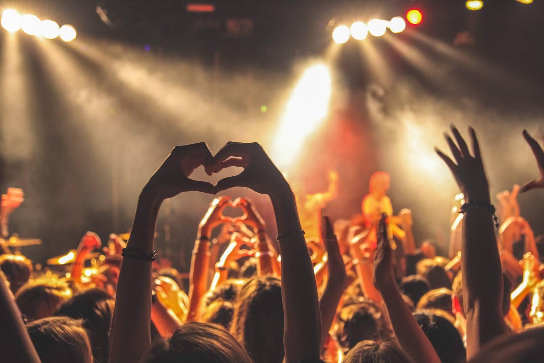 Immagine di una persona ad un concerto che fa la forma di un cuore con le mani.