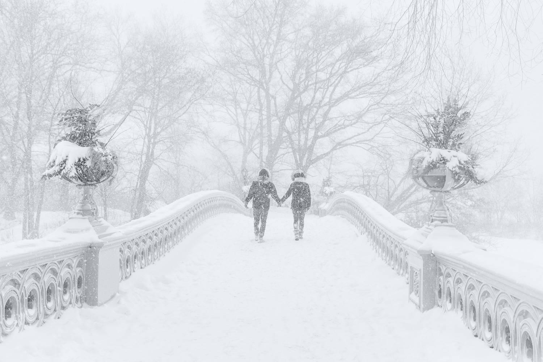 Immagine di una coppia che cammina sul Bow Bridge ricoperto di neve a Central Park, New York