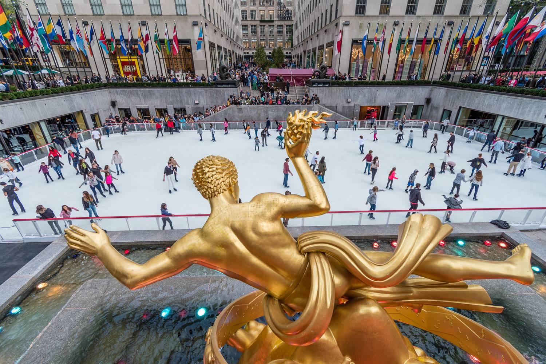 Immagine della pista di pattinaggio al Rockefeller Center con una statua d'oro, bandiere internazionali e persone che pattinano