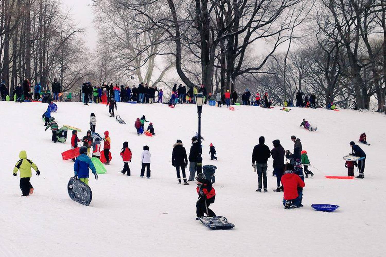 Immagine di bambini che giocano con la slitta giù per una collina coperta di neve