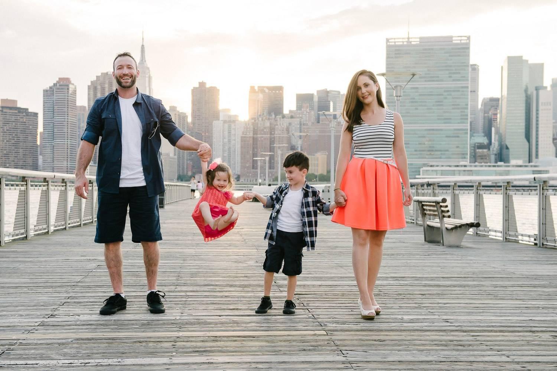 Immagine di una famiglia che passeggia con i bambini con un grattacielo di New York sullo sfondo (Photo credit: Kimberly for Flytographer in NYC)
