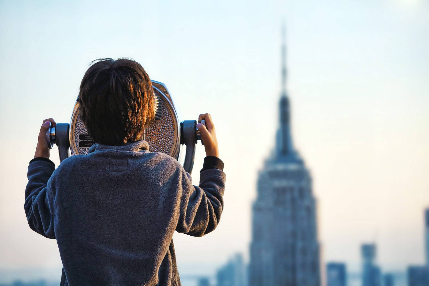Immagine di un bambino che guarda dal telescopio all'Empire State Building (Photo credit: Unsplash)