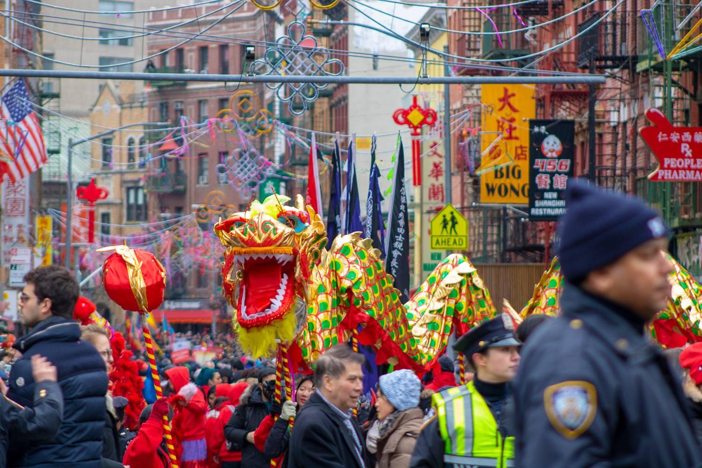 Immagine di una strada di Chinatown durante la parata per il Capodanno cinese con un dragone e la polizia di New York