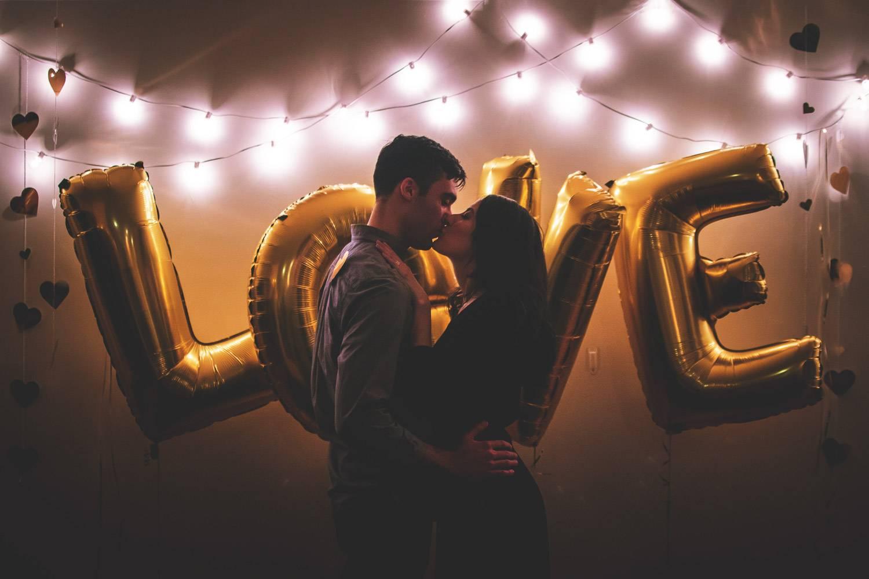 """Foto della parola """"love"""" scritta su palloncini dorati e una coppia che si bacia nel buio con fili di luci dietro"""