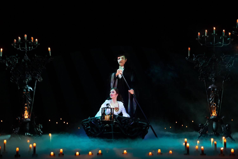 Foto dal Fantasma dell'Opera a Broadway con i personaggi principali in barca al buio circondati da candele