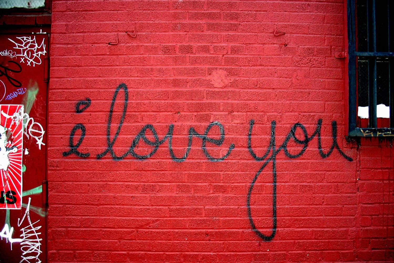 """Foto della parola """"love"""" scritta in nero su un muro di mattoni rossi"""
