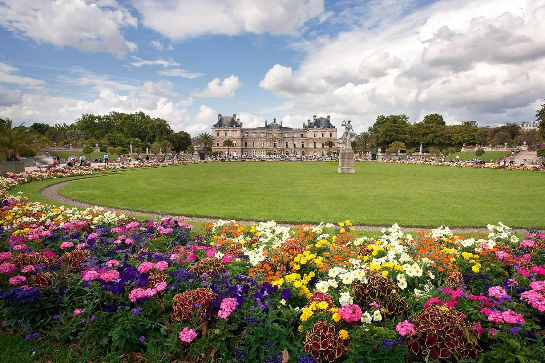 Foto dei Giardini del Lussemburgo a Parigi con un grande ovale di erba verde circondato da fiori colorati