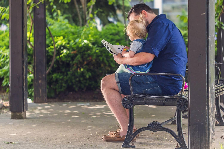 Foto di un padre seduto al parco con un bambino sulle gambe mentre legge un libro