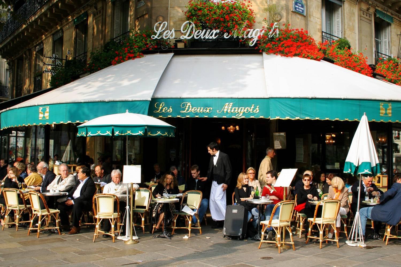 Foto della facciata del ristorante di Parigi Les Deux Magots con persone sedute ai tavolini fuori