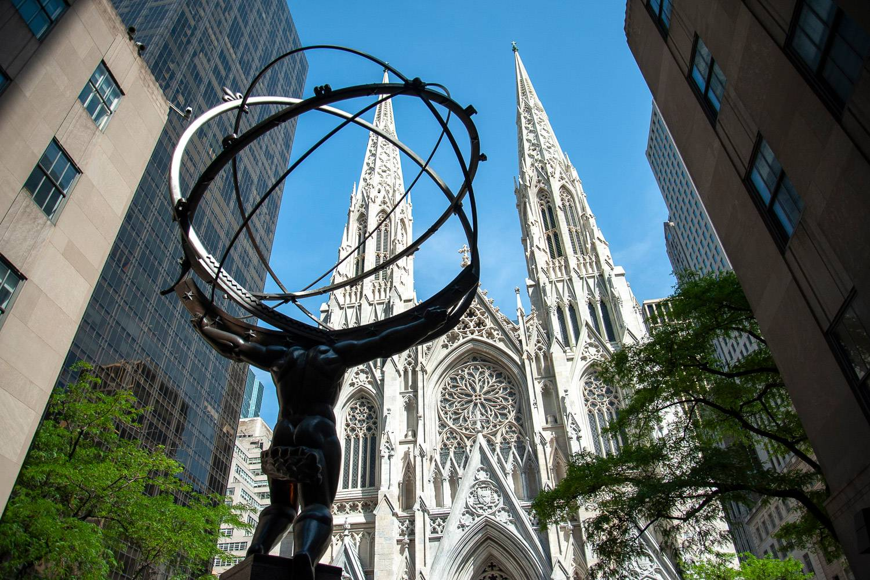 Immagine della Cattedrale di San Patrizio nel centro di Manhattan con la statua di Atlante con il mondo sulle spalle in primo piano