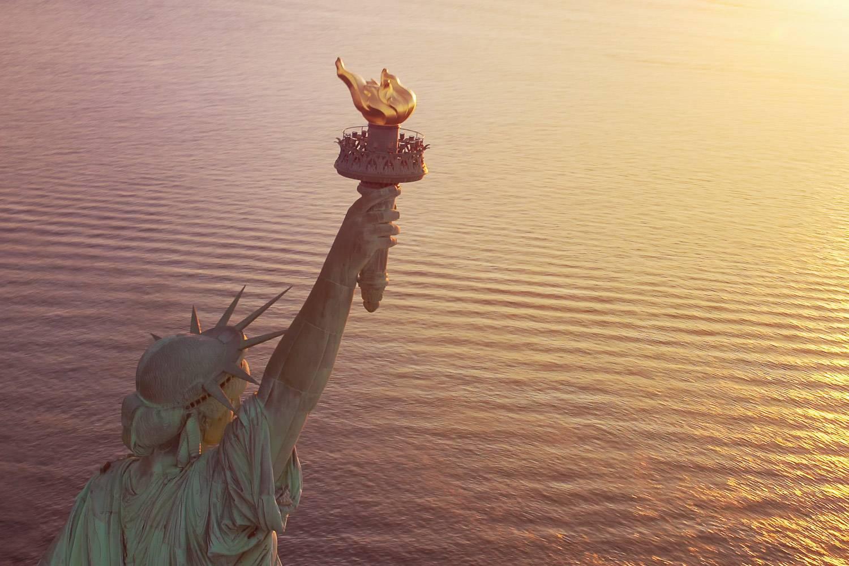 Immagine in primo piano della Statua della Libertà con la torcia d'oro sull'acqua al tramonto